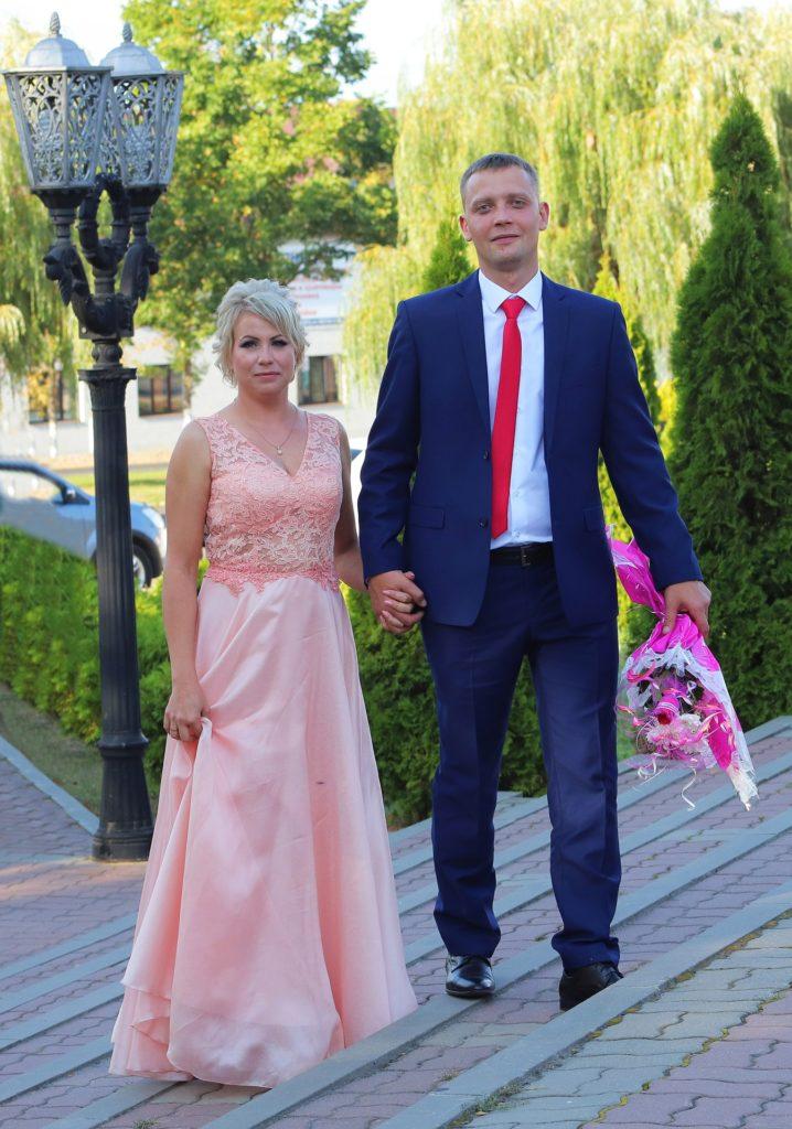 bride in pink dress with groom & flowers