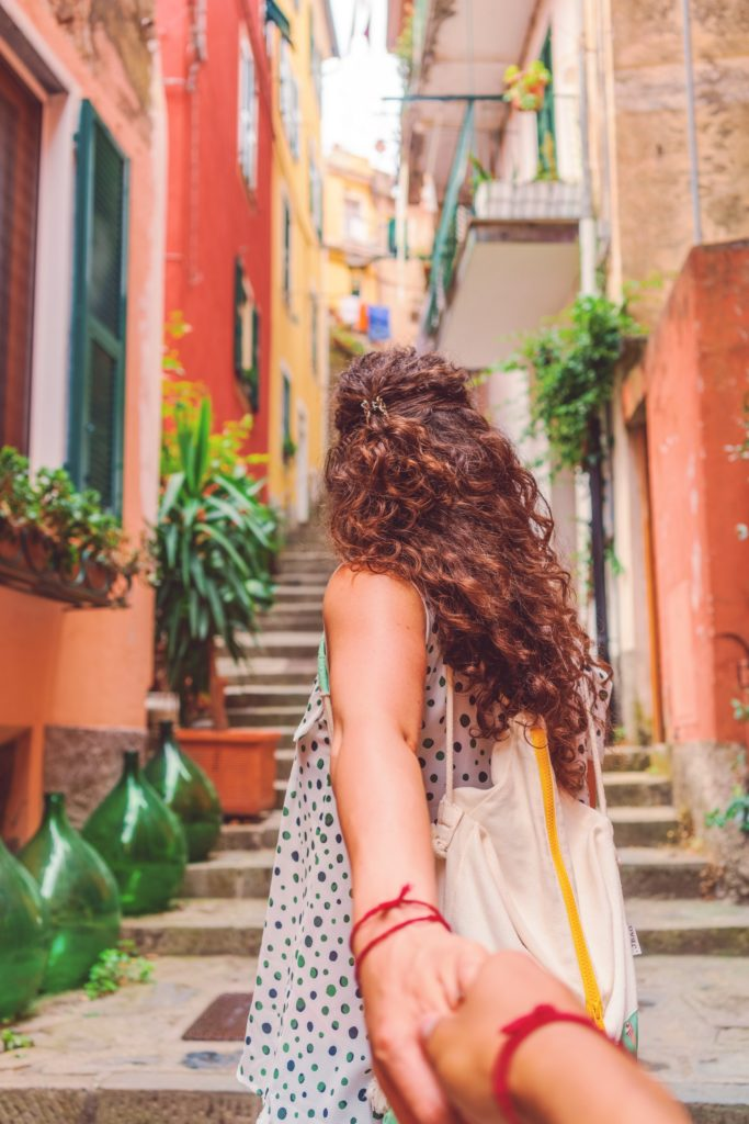 woman leading man up stairs in italy